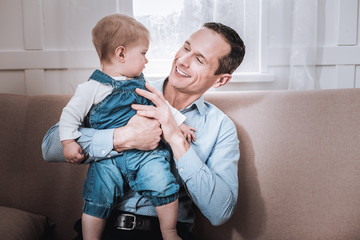 Nice positive man spending time together with his child