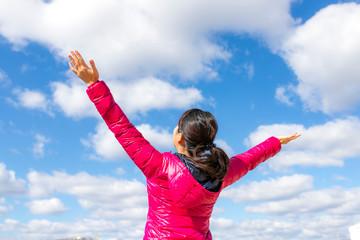 青空に向かって両手を広げる女性