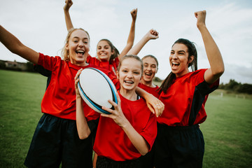 Cheerful female rugby players celebrating