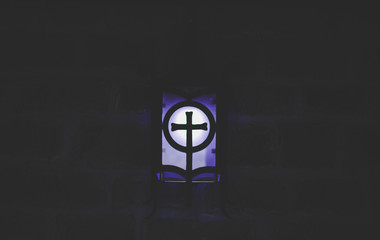 abstract cross religion sign blue light lantern illumination in darkness and shadows of underground cave