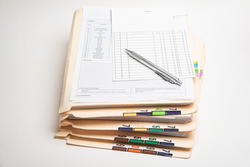 A stack of color-coded and numbered patient medical records with blank doctor's office visit form, ledger card, and ballpoint pen.