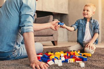 Adorable boy assembling construction set with grandparent