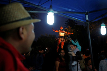 """A giant puppet known as """"The Dancer"""" is transported through the street as part of a performance by Spanish street theatre company Antigua i Barbuda during the Santiago a Mil International Theatre Festival in Santiago"""