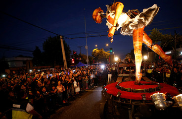 "A giant puppet known as ""The Dancer"" is transported through the street as part of a performance by Spanish street theatre company Antigua i Barbuda during the Santiago a Mil International Theatre Festival in Santiago"