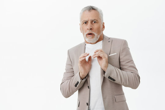 Portrait of intense displeased old male man in elegant suit holding hands pressed to chest stepping backwards from dislike and aversion feeling creepy and timid posing against white background