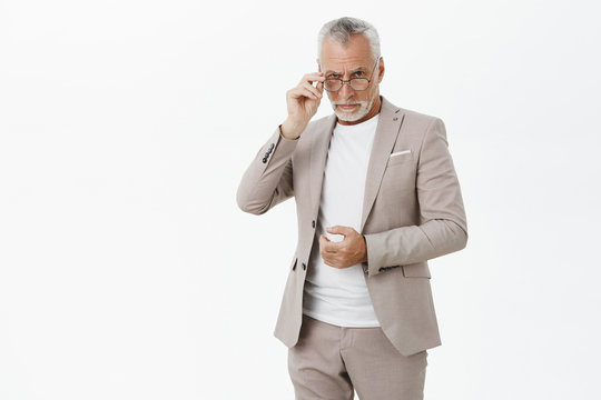 Portrait of serious good-looking wise male entrepreneur in glasses with white beard and hair touching suit and frames looking from under forehead intelligent and questioned posing over grey wall