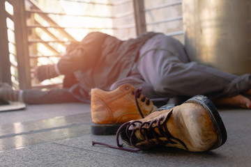 Old shoes and homeless. Homeless man is lie down on walkway in town.He is  hoping to have the better life. poverty, despair, Photo Sympathetic and hope concept.