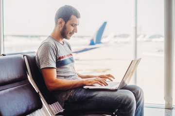 Young man using laptop in airport terminal
