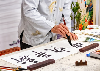 Asian caligraphy. The master of Chinese Caligraphy writes on rice paper characters and hieroglyphs that read Xin nian kuai le and are translated as Happy New Year.