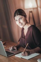 Cheerful female freelancer noting down