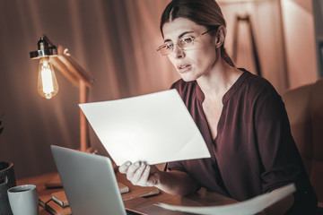 Attentive female freelancer examining documents