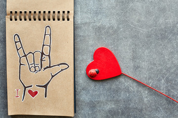 A notebook of Kraft paper, with a painted ASL (American sign language) symbol I Love you (ILY) and a wooden red heart with a small ladybug. Suitable for congratulations to the holiday Valentine's day