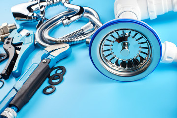 plumbing tools and equipment on blue background.