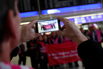 Union members with a banner pose for a picture during a strike at Germany's largest airport in Frankfurt