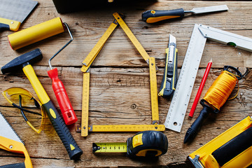 set of construction tools on a wooden background top view