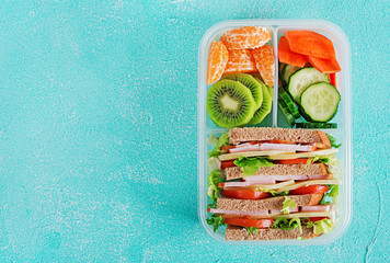 Foto auf Leinwand Sortiment School lunch box with sandwich, vegetables, water, and fruits on table. Healthy eating habits concept. Flat lay. Top view
