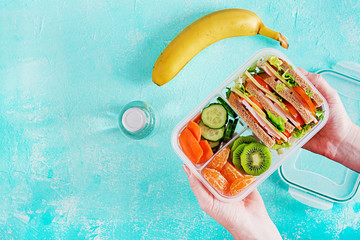 Fotobehang Assortiment Lunchbox in hands. School lunch box with sandwich, vegetables, water, and fruits on table. Healthy eating habits concept. Flat lay. Top view