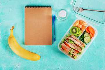 Foto op Canvas Assortiment School lunch box with sandwich, vegetables, water, and fruits on table. Healthy eating habits concept. Flat lay. Top view
