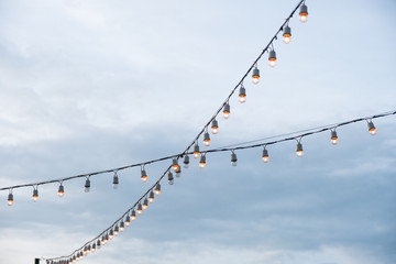 Antique light bulbs crossing with hanging on wire