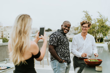 Diverse friends getting their picture taken at a rooftop party