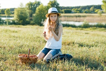Outdoor summer portrait of little girl with basket strawberries, straw hat. Nature background, rural landscape, green meadow, country style