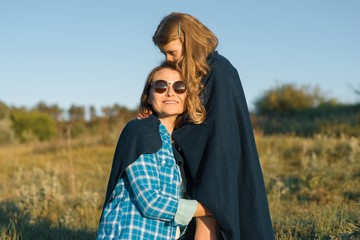 Portrait of parent and child. Happy mother and little daughter hugging together. Nature background, rural landscape, green meadow