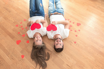 Top view of happy young couple with paper hearts.