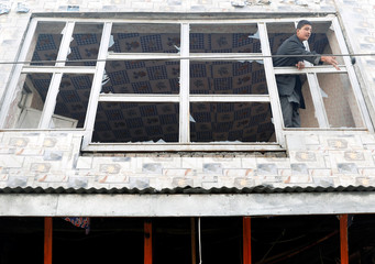 An Afghan man removes broken glass from a window after a car bomb blast in Kabul