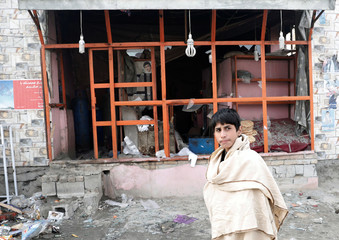 An Afghan boy walks past a damaged bakery at the site of a car bomb blast in Kabul, Afghanistan