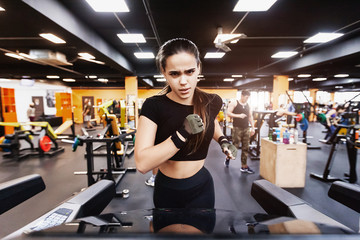 Portrait of a serious hardy young girl running on a treadmill after a strength training in the hall. Concept of goal and fit shape without fat