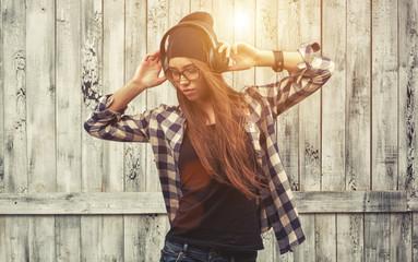 Hipster girl in glasses, headphones and black beanie