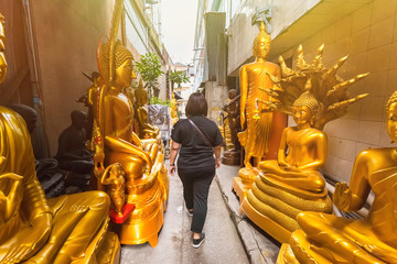 Woman was walking through golden buddha road in Bangkok Thailand.