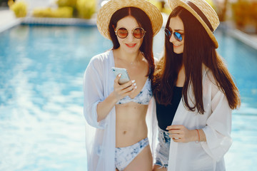 two girls relaxing by the pool