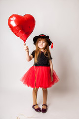 stylish little girl on red dress  holding a red ball in the form of heart .Valentine's day.