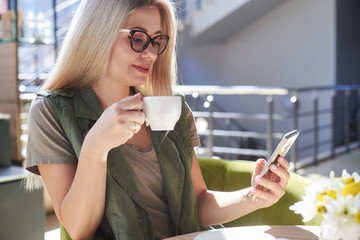 Beautiful woman using mobile phone at cafe