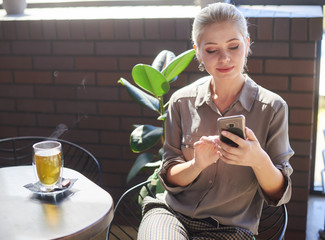 Beautiful woman using phone at cafe