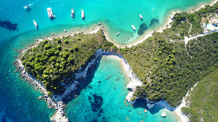 Aerial drone bird's eye view photo of sail boats docked in tropical caribbean paradise bay with white rock caves and turquoise clear sea Wall mural