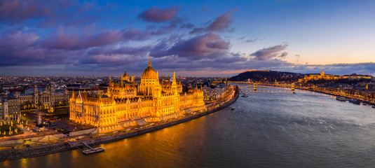 Poster Budapest Budapest, Hungary - Aerial panoramic view of the beautiful illuminated Parliament of Hungary with Szechenyi Chain Bridge, Buda Castle Royal Palace and colurful clouds at background at sunset