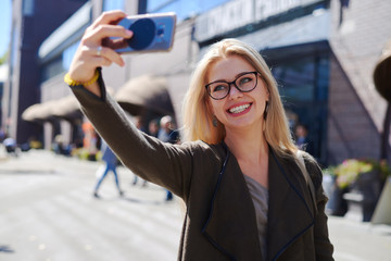 Woman taking selfie using mobile camera in city