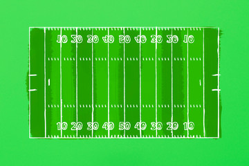Image of a football field on a green cardboard. Tactics of the game. The concept of the game of American football. Flat lay, top view.