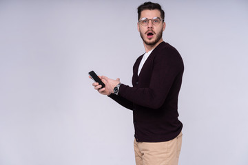 You will have problems man! Portrait of angry confused aggressive in bad mood guy shouting threatening in the loud-speaker of his smartphone, isolated on gray background.