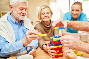 Senioren stapeln zusammen bunte Bausteine