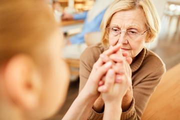 Altenpflegerin tröstet eine demente Seniorin