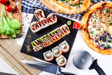 Food party table concept. Top view on snack pizza and sushi. Italian and Japanese cuisine on white wooden background with free copy space for text, logo or brand. Picture for restaurant