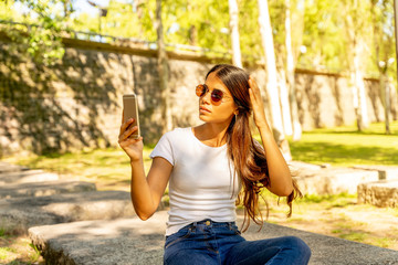 A beautiful young woman in a white shirt taking a selfie while sitting on a concrete block on a sunny day.