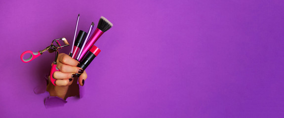 Woman hand with professional cosmetic tools for make up: brushes, mascara, lipstick, eyelash curler on violet background. Beauty concept. Banner for cosmetics sale. Copy space Wall mural