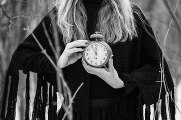 Close up image of woman holding vintage clock that shows five to twelve time.
