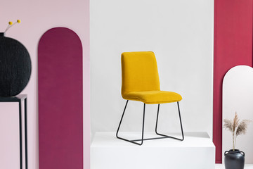 Stylish yellow chair in the middle of elegant showroom with white and purple walls