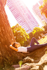 A beautiful young woman in a white shirt and sunglasses laying next to a tree and enjoying the sunshine.