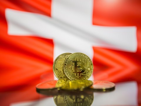 Bitcoin gold coin and defocused flag of Switzerland background. Virtual cryptocurrency concept.